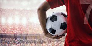 Jugador de fútbol sujetando una pelota